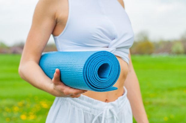 woman-standing-and-holding-blue-yoga-mat-2394051